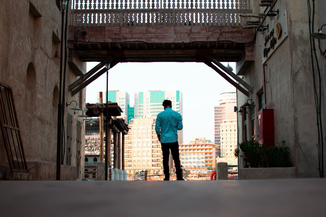 A person walking down a street next to a building